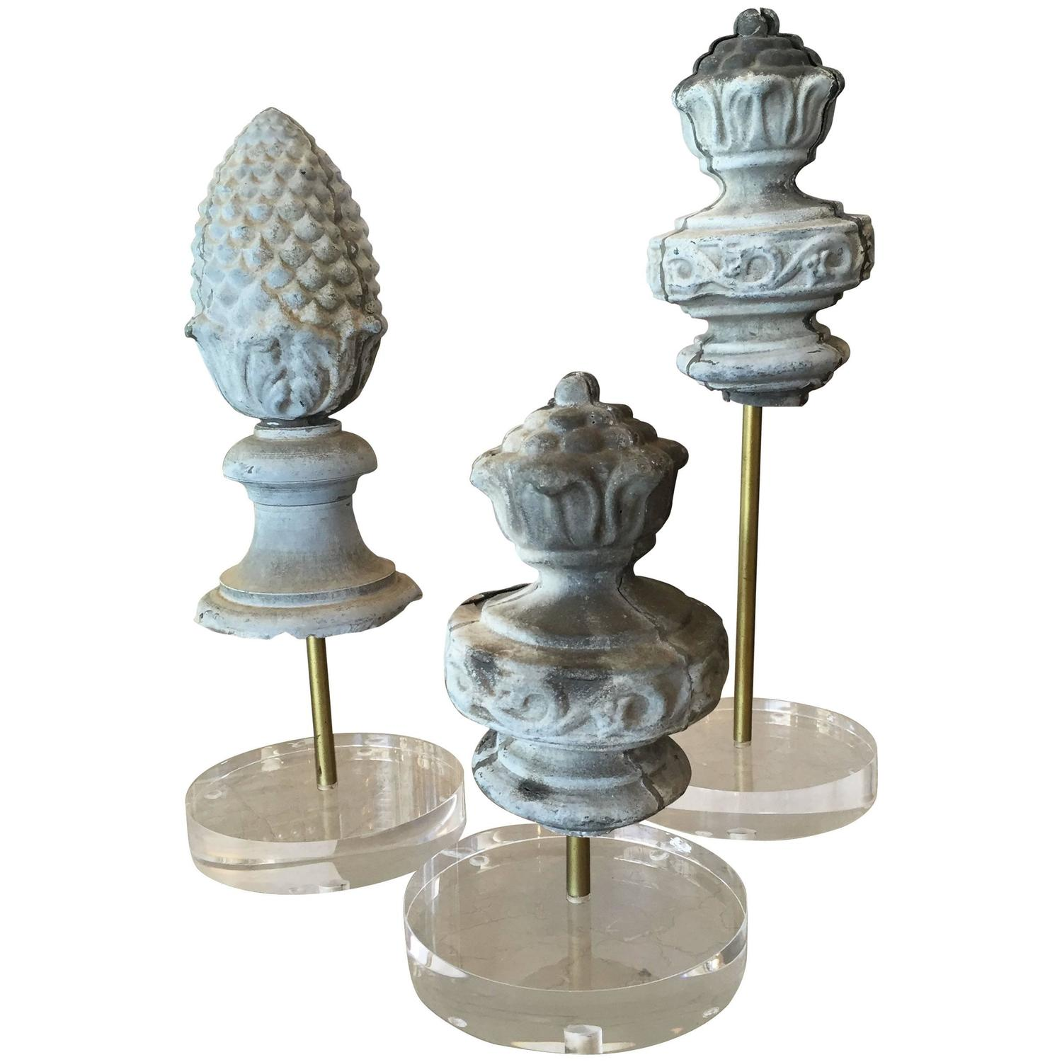Antique zinc artifacts mounted on brass poles and lucite bases. I love the juxtaposition between the old and new.    Collection available at  Shop Tiffany .