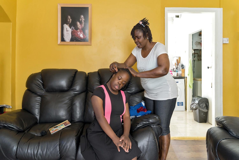 Olu fixing Christiana's hair
