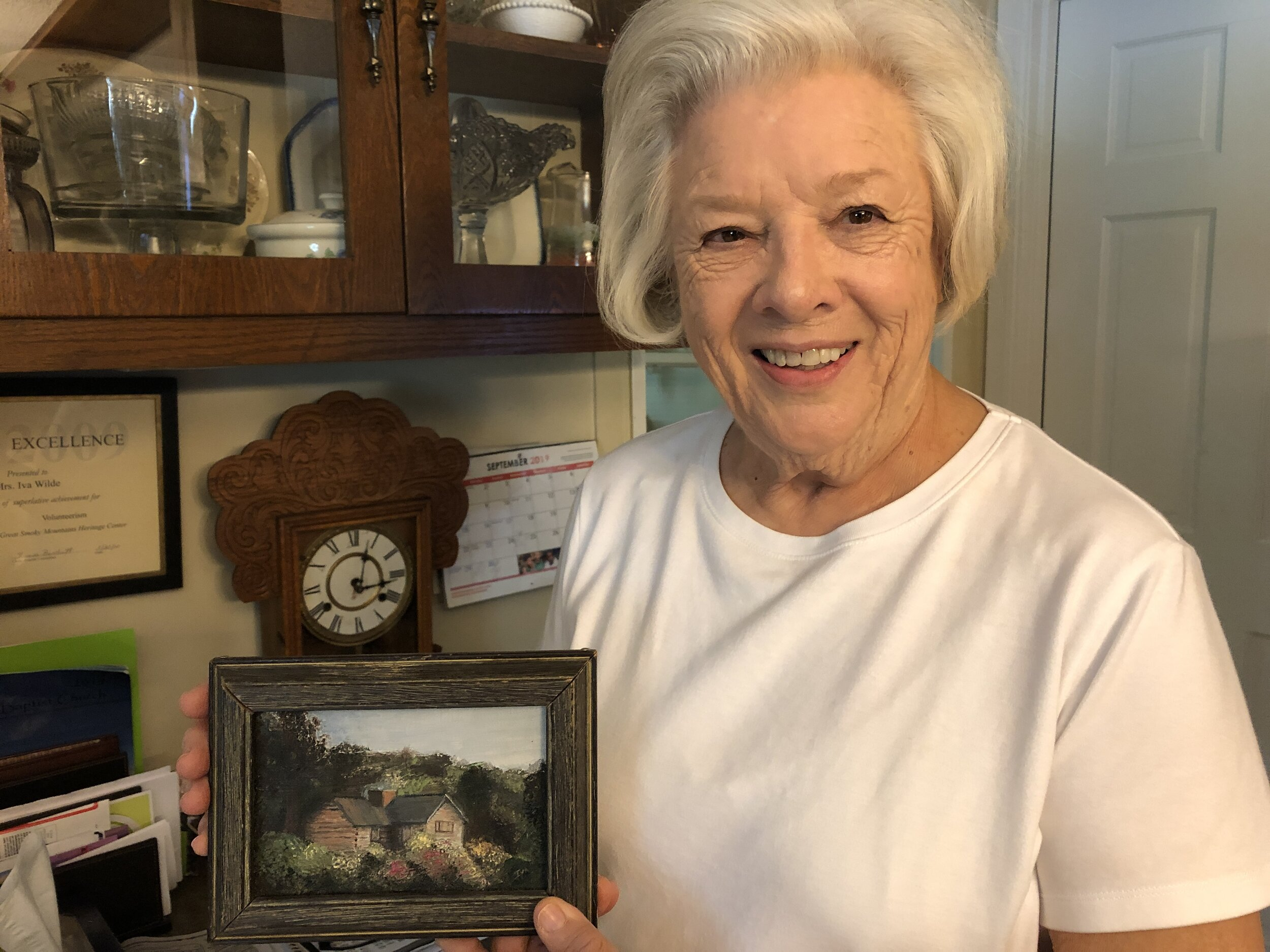 Iva holds a painting that she painted of a structure on top of Mount LeConte. Iva and her family used to hike to Mount LeConte and she has very fond memories of these times.