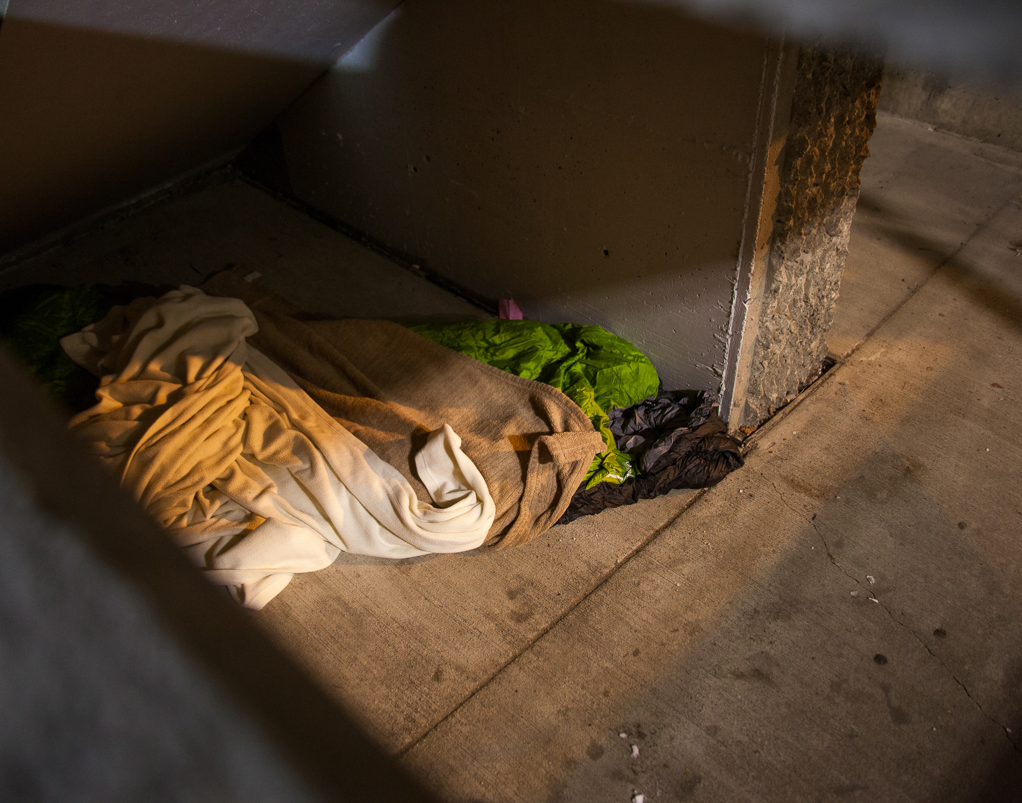 Hidden behind a cement wall and a stair case, some youth find shelter in parking garages.