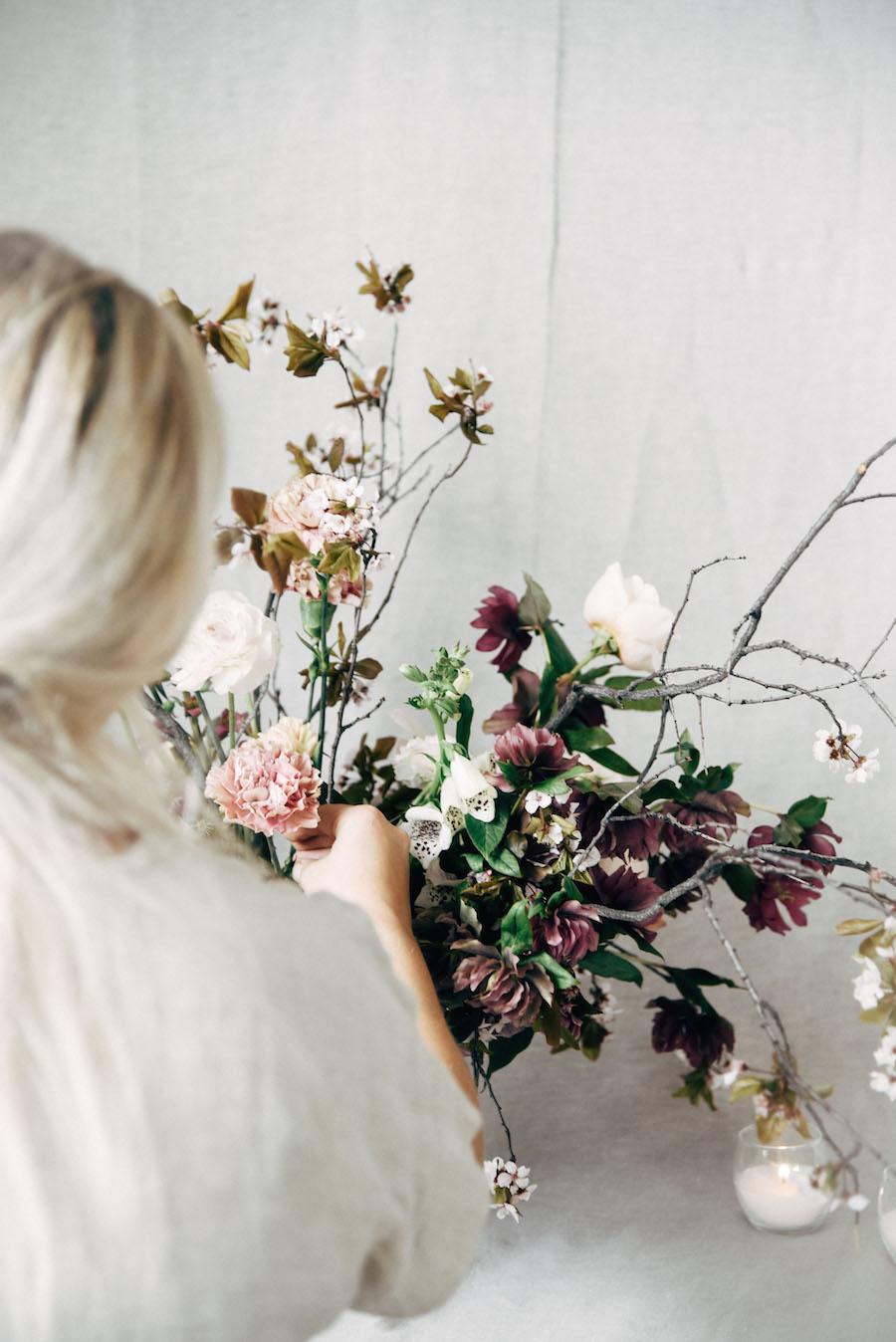 Nicole Land of Soil & Stem adjusting a flower arrangement at her Spring Floral Design Workshop now featured on Cottage Hill