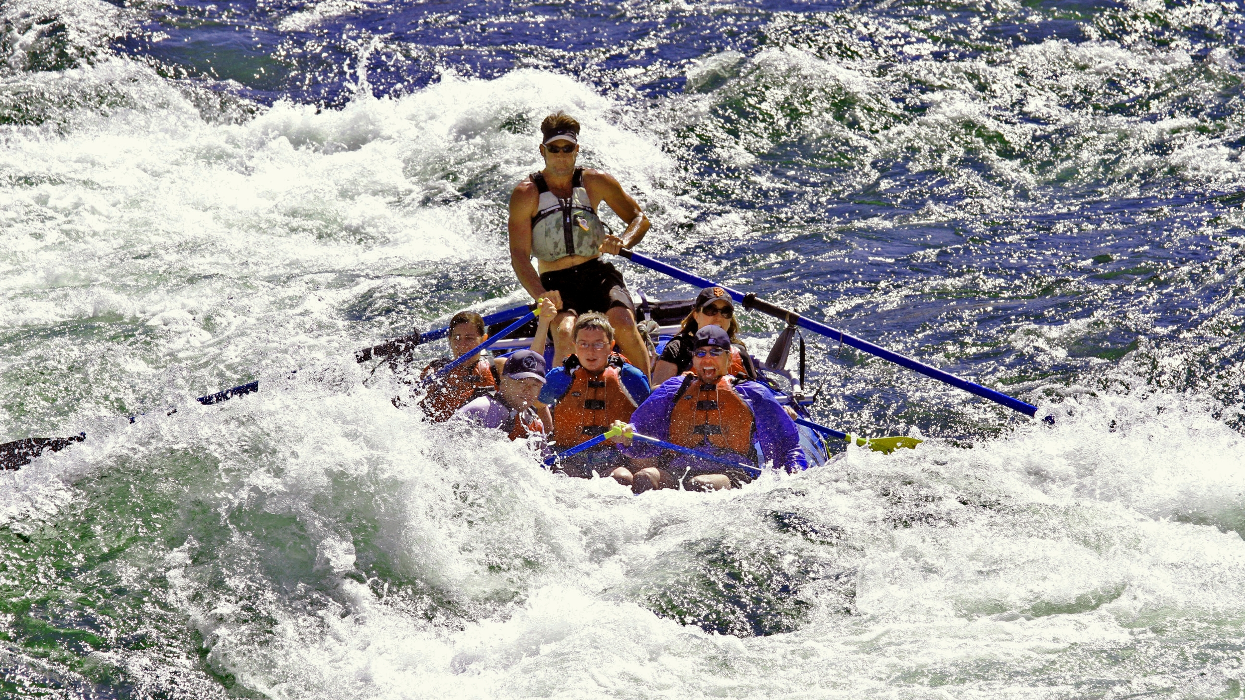Raft of kids disappearing behind a big whitewater wave while rafting on the Salmon River.
