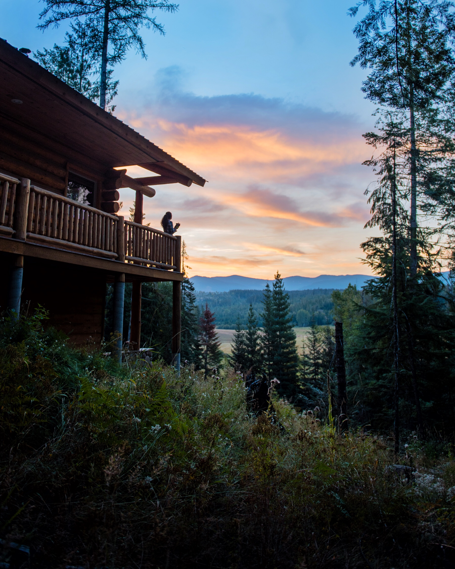"Our cabin, the aptly named ""Meadow view"" looking towards the Cabinet Mountains at sunrise. Two stories with three beds, a kitchen, fireplace, and a wrap around deck."