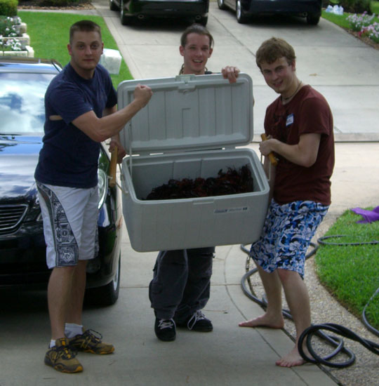 My nephew (left), our son's childhood friend (middle), and our son (right) tote a cooler of live crawfish to the cook. Make special note that our nephew is toting his side one-handed and flexing with his other. LOL.