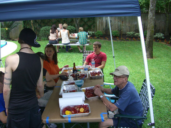 We set up tents and tables in the backyard and serve the crawfish in aluminum tubs. At the table, from left to right: Our youngest son (with his back to us), my brother-in-law's girlfriend, my nephew and Greg's dad. Sitting at the picnic table in the distance are our cousins.