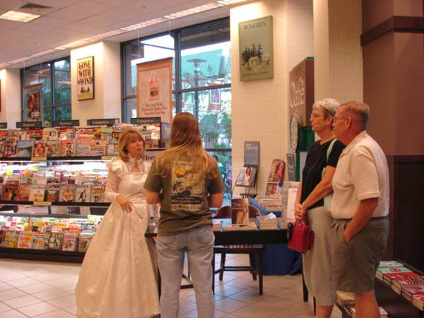 Visiting with some readers at my book signing while wearing a replica of a 17th century wedding gown.