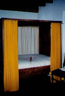 """This is an interior shot of the Master's Chamber of Bacon's Castle. Once again, I took the liberty of borrowing. In this case, I borrowed the bed. The tick (mattress) is supported by rope. Do you see the bed key laying on the bedsheets? When the supporting ropes would slacken, you would have to wedge your bed key between the rope and the bed frame, then twist--thus tightening the rope. Next, you would release the wooden peg from the section you just did and move to the next section. Once you got all the way around, you could """"sleep tight."""" If it was a straw mattress, though, the chances were that the bed bugs would bite!"""