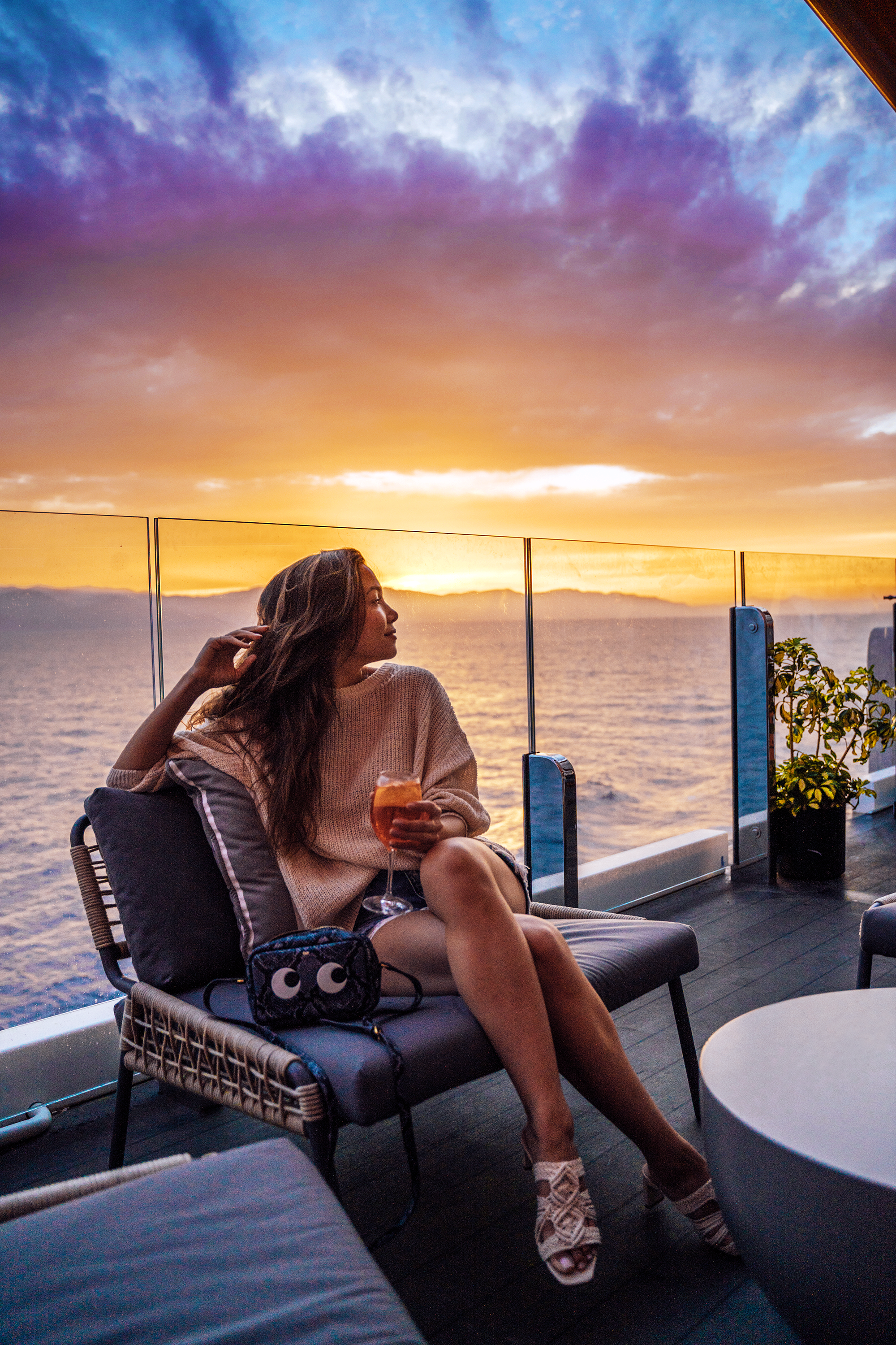"My handbag clearly knew what to look at. :) Catching one of many spectacular sunsets from the Celebrity Edge's ""Magic Carpet"", a lounge on the exterior of the ship that moves vertically, like an elevator, between the 2nd and 16th decks."