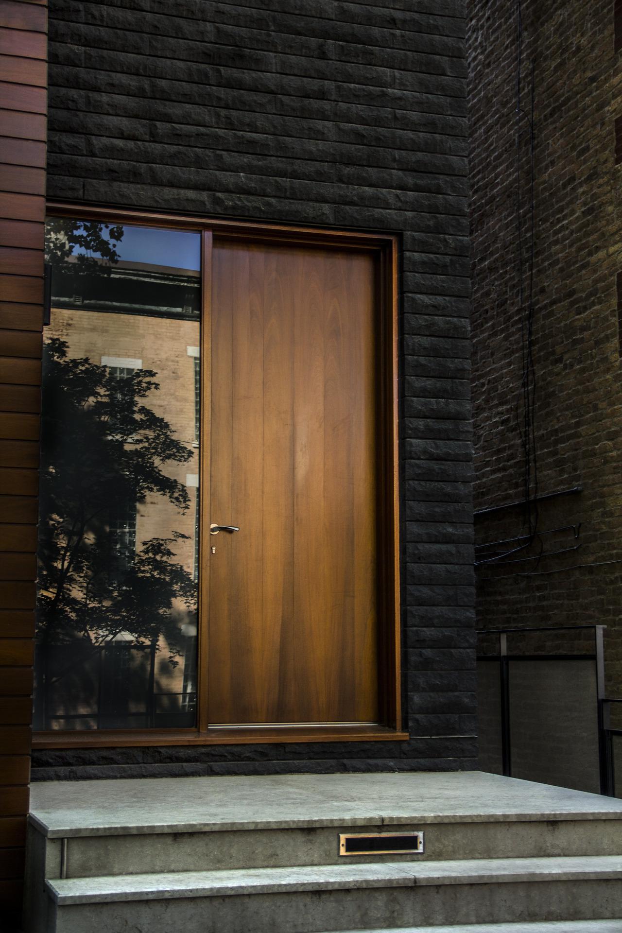 Dark bricked wall with wooden door constrast  ITCHBAN.com