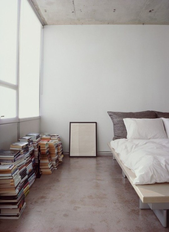 Loft styled bedroom with stacks of books ITCHBAN.com
