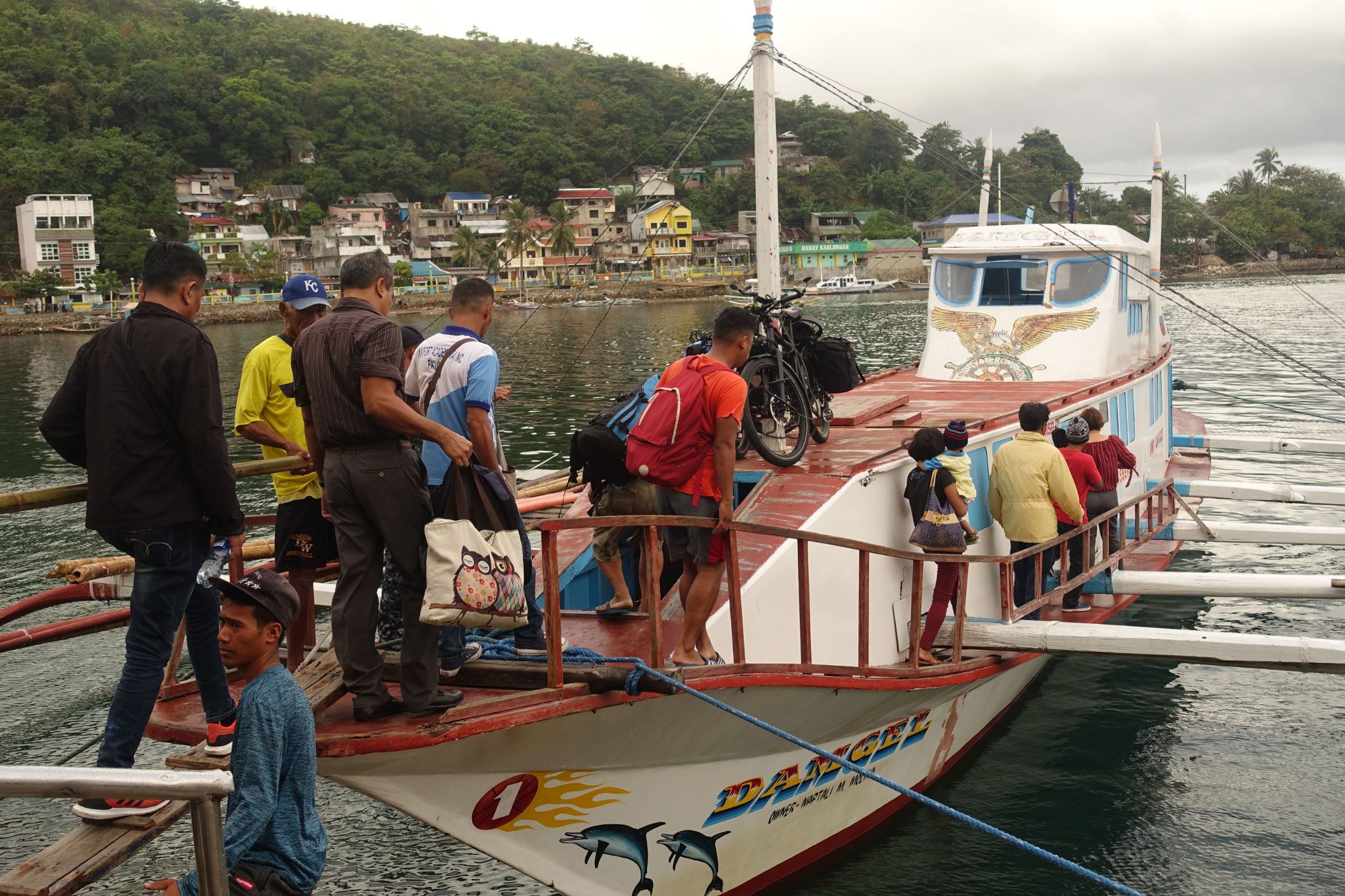 Many different boat styles make travel interesting. The man in the yellow T-shirt is one end of the hand-rail!