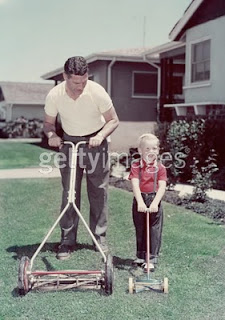 Father + son w. push mower, circa 1960 gettyimages.com