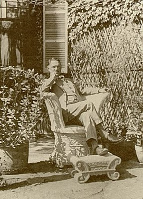 Fletcher Steele reclining in stone chair, afternoon garden