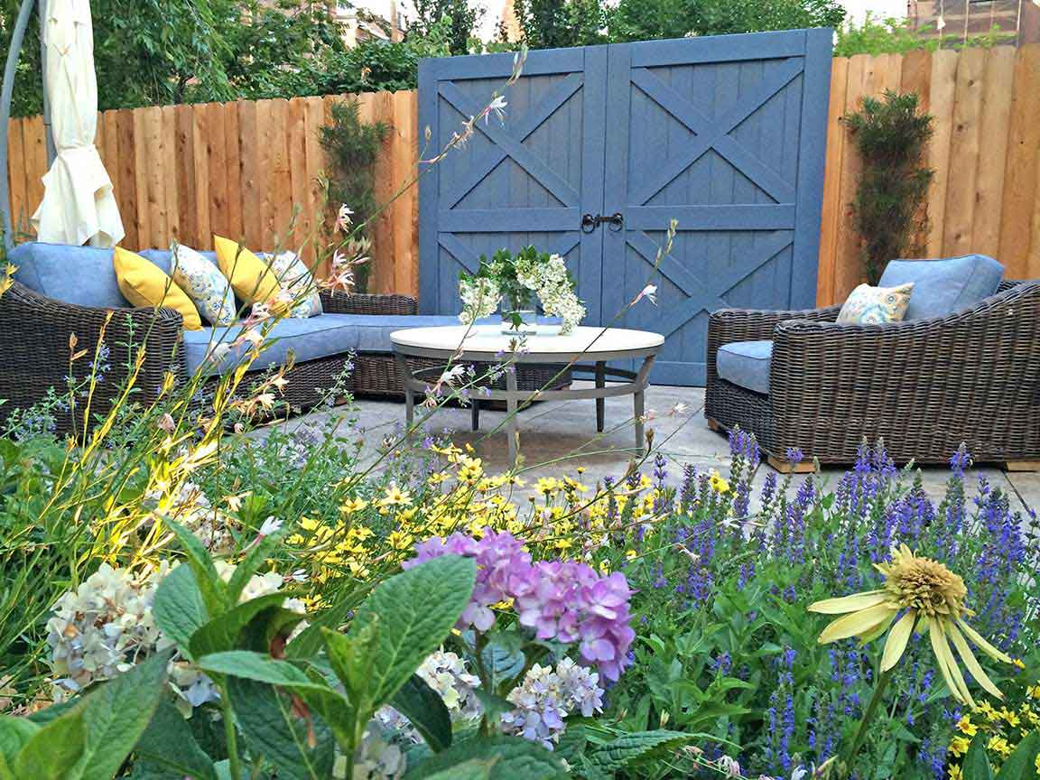 A Brooklyn garden design by Todd Haiman Landscape Design. One of several gathering areas within this large urban outdoor property in Park Slope, evoking a walk though the french countryside.. hence the whimsical barn door. photo©ToddHaimanLandscapeDesign2016