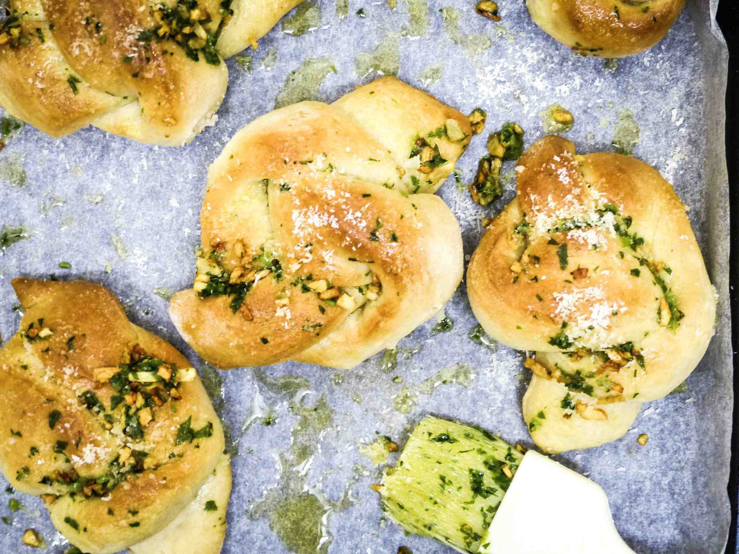 Brushing the garlic butter dressing and sprinkling sea salt and cheese on each knot.