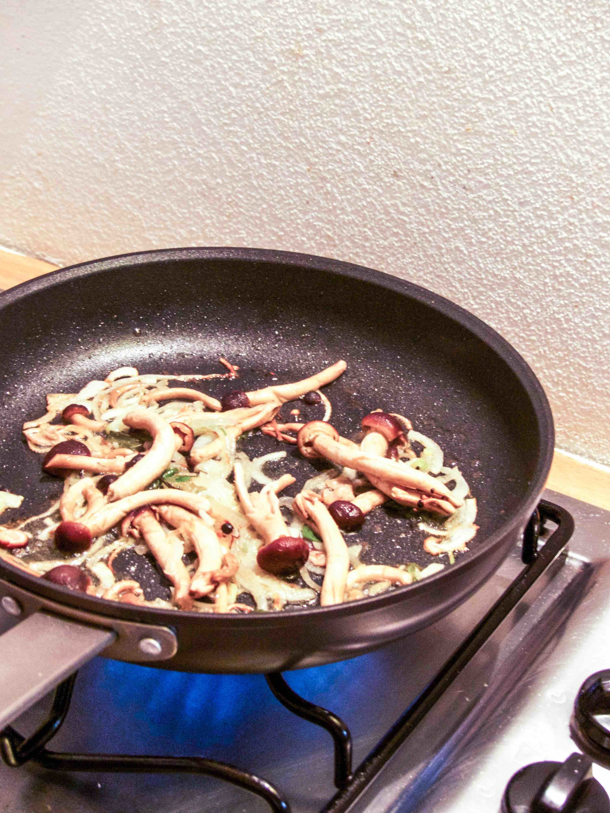 Preheat a skillet with a drizzle of olive oil on medium heat, cook onion for 3-4 minutes until they turn translucent.  Add mushrooms and a splash of sake.  Season.  After the alcohol has evaporated, put a lid on and cook for another 3-5 minutes.
