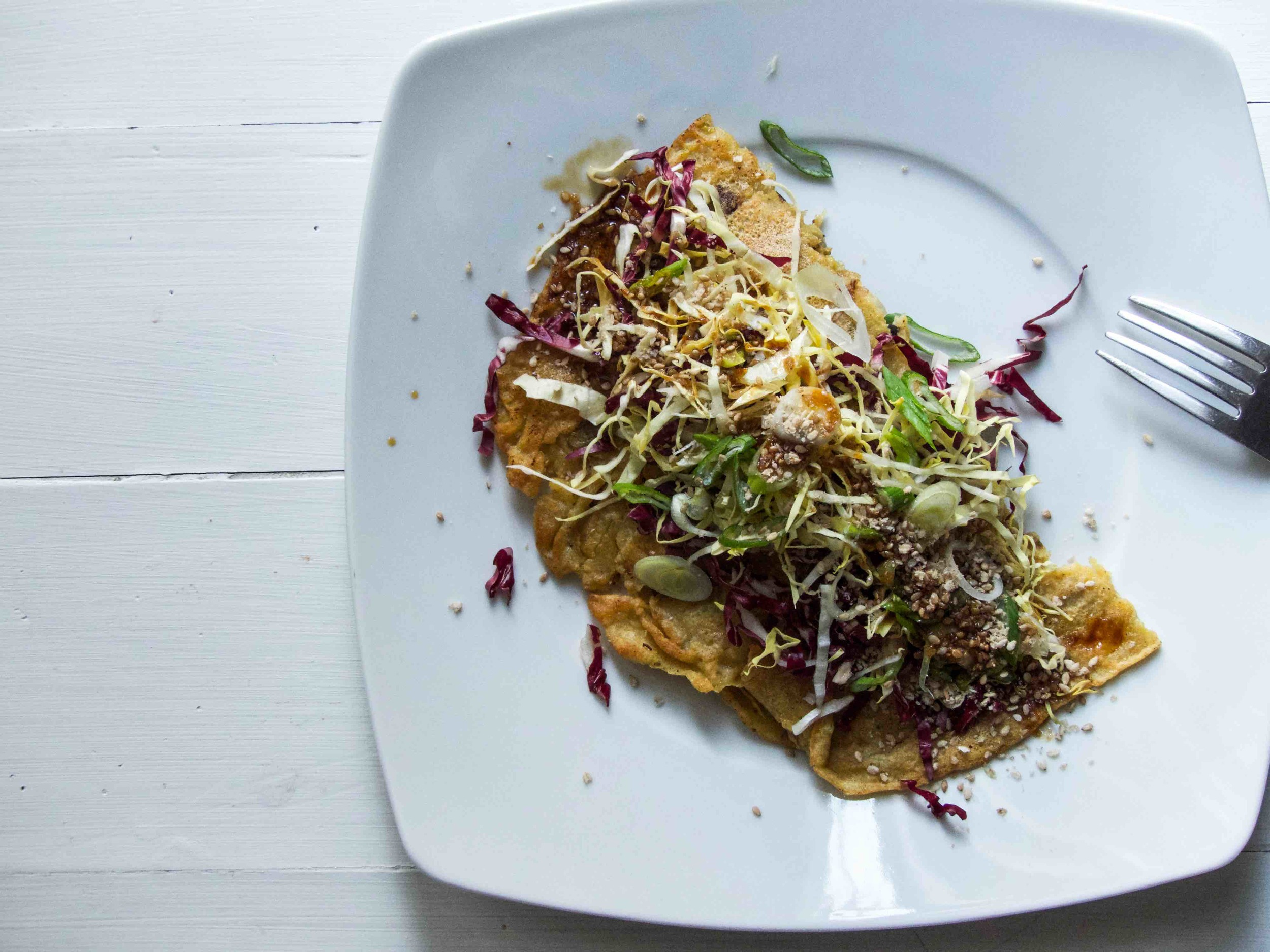 Transfer the omelette to a plate and start garnishing with shredded cabbage, radicchio, grinded sesame seeds, and chopped spring onion.