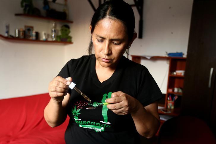 Ana Álvarez sirve una cucharada de aceite de marihuana a su hijo Anthony en su residencia en Lima. Foto de Newspaperon.com.