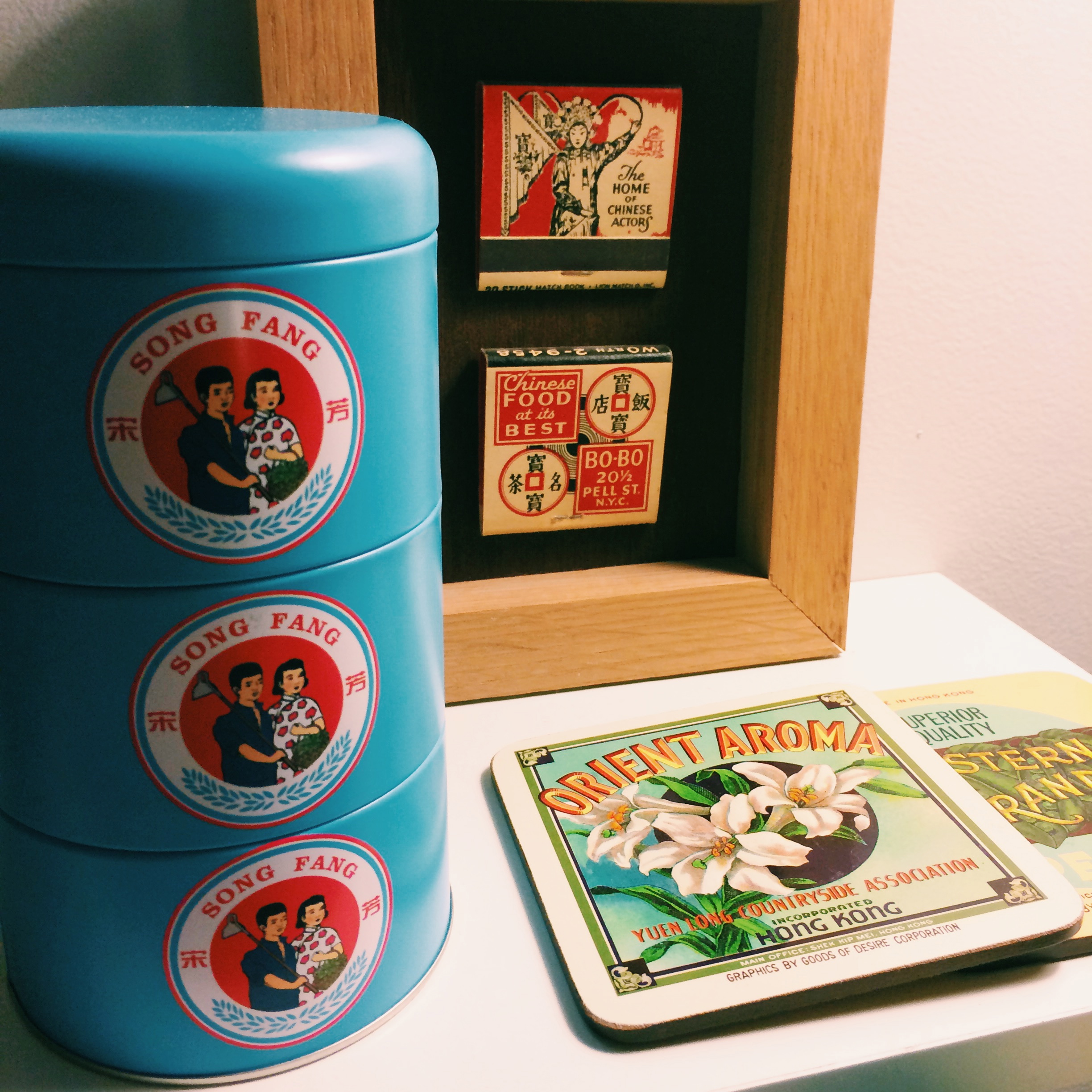a stacked tin from song fang maison de thé  in shanghai; framed matchbooks from chinatown restaurants; and coasters from  goods of desire  in hong kong.
