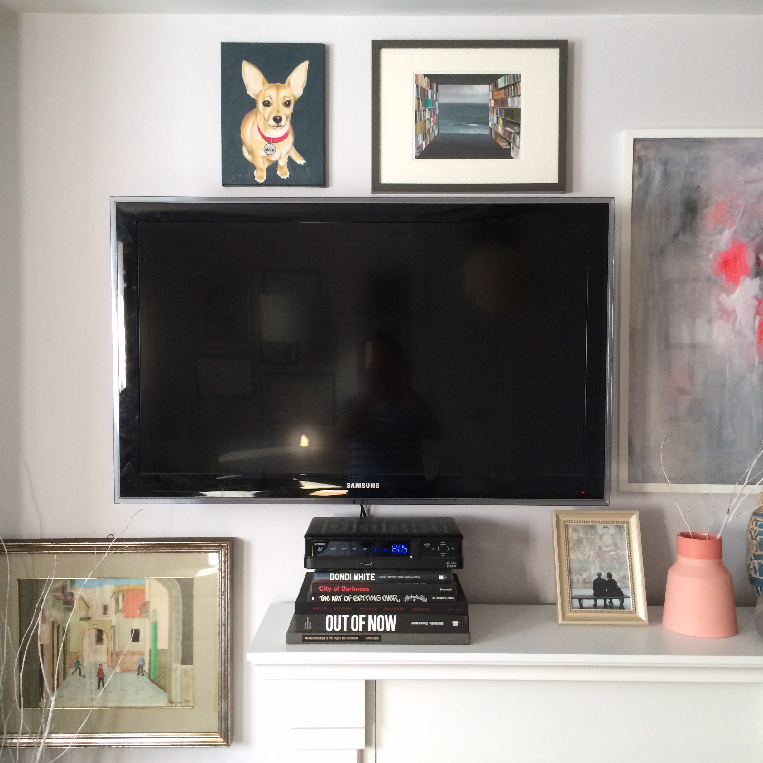 the whole point of the gallery wall is to camouflage the tv. did it work? the stack of books holds the cable box and masks the cables, which drop down behind the fireplace.