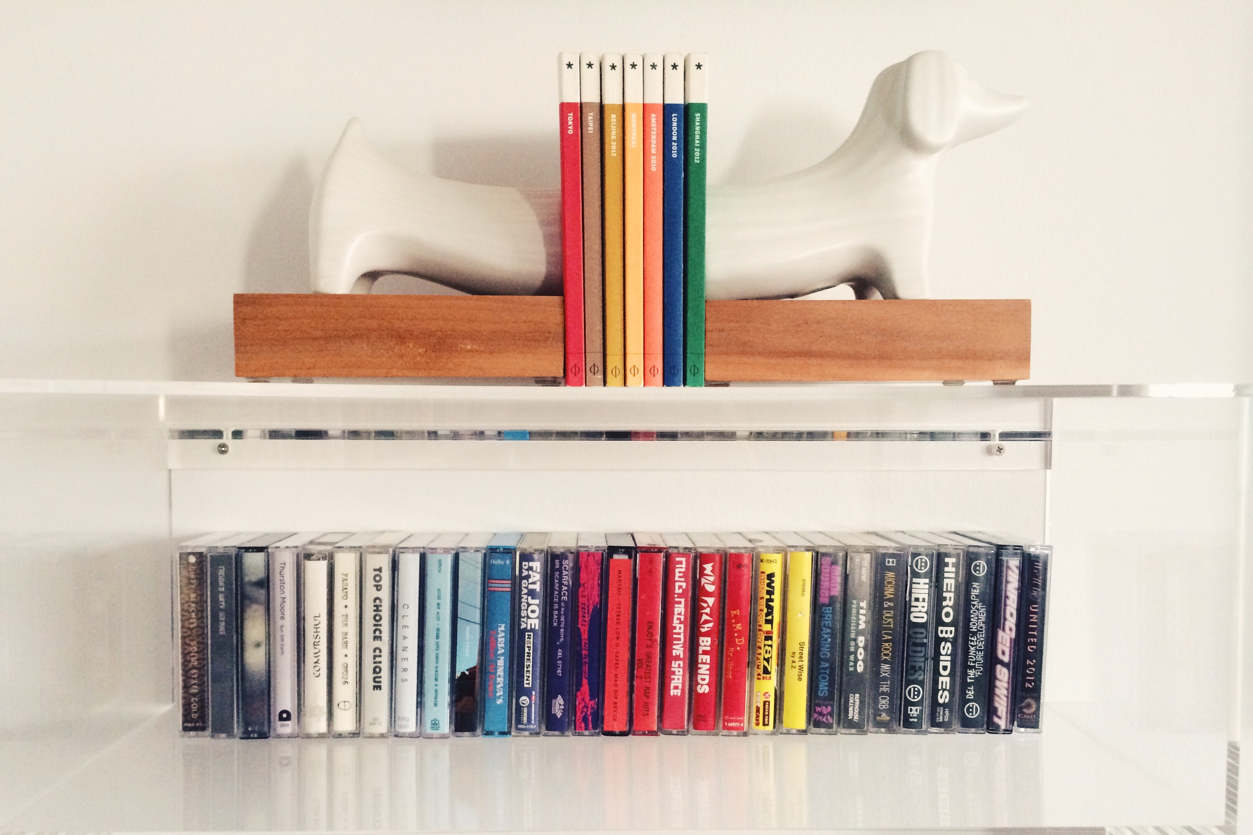 i grabbed the dachshund bookends from a  jonathan adler  warehouse sale a few years back. the  acrylic shelf  is from cb2. the books are  wallpaper city guides , and the tapes are hhh's.