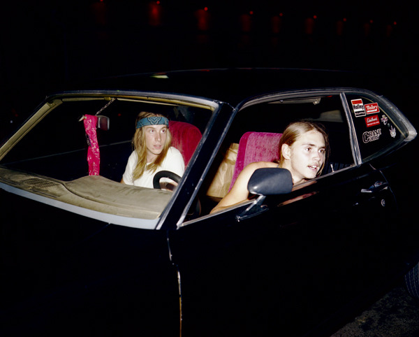 Stoners, Asbury Park, New Jersey, 1980, by Joe Maloney. Medium view of two young adult men with long hair in a black car with red seats at night.