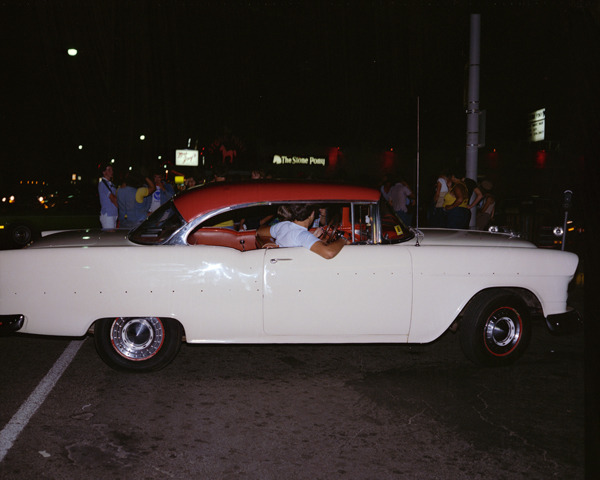 Chevy, Asbury Park, New Jersey, 1980, by Joe Maloney. Digital archival pigment print of people inside a white Chevy car with a red roof, at night.