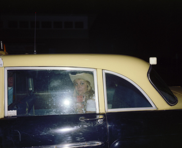 Girl in Cab, Asbury Park, New Jersey, 1980, by Joe Maloney. Digital archival pigment print of a blonde girl wearing a white cowboy hat in back of a taxi.