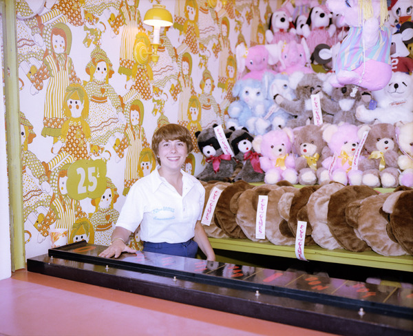 Girl with Stuffed Animals, Asbury Park, New Jersey, 1980, by Joe Maloney. Digital archival pigment print of a girl in front of stuffed toy game prizes.