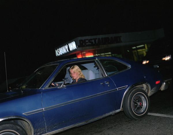 Asbury Inn, Asbury Park, New Jersey, 1980, by Joe Maloney. Digital archival pigment print of blonde girl in a blue car, in front of the hotel at night.