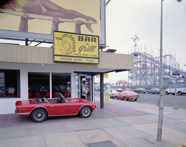 Gold Digger, Asbury Park, New Jersey, 1980, by Joe Maloney. Digital archival pigment print of a red convertible parked in front of the bar on the street.