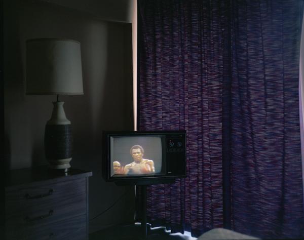 Sugar Ray Empress Match, Asbury Park, New Jersey, 1980, by Joe Maloney. Digital archival pigment print of a boxing match on TV, inside a dark room.