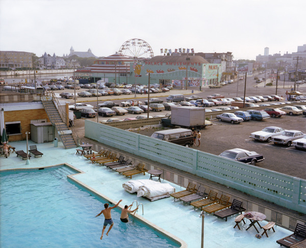 View from Empress Hotel, Asbury Park, New Jersey, 1980, by Joe Maloney. Digital archival pigment print of view from hotel of kids jumping into a pool.