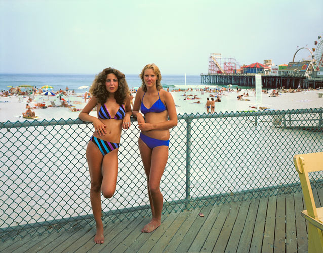 Two Girls, Seaside Heights, New Jersey, 1980, by Joe Maloney. Digital archival pigment print of two girls in bikinis leaning on fence near the beach.