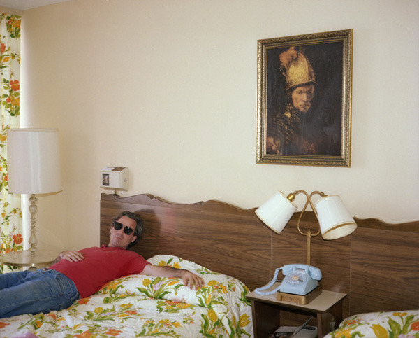 Victor, Metropolitan Motel, New Jersey, 1980, by Joe Maloney. Digital archival pigment print of a man in red shirt on a hotel bed wearing sunglasses.