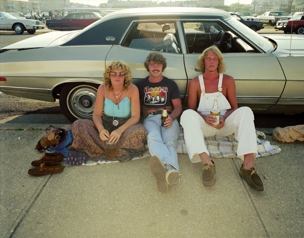 Rockers, Asbury Park, New Jersey, 1980, by Joe Maloney. Digital archival pigment print of three seated people seated on ground, leaning on a car.