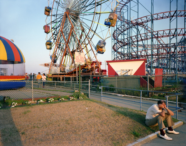 White Shoes, Asbury Park, New Jersey, 1980, by Joe Maloney. Digital archival pigment print of a seated man in white shoes, in front of amusement park.