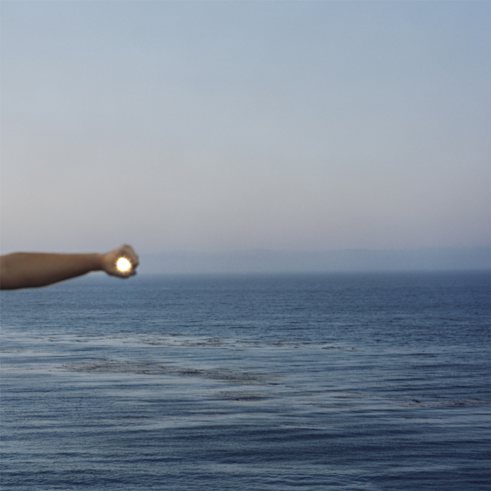 I Control the Sun #1, 2013, by Lilly McElroy. Archival pigment print of the artist's arm and hand extended above the sea, encircling the setting sun.