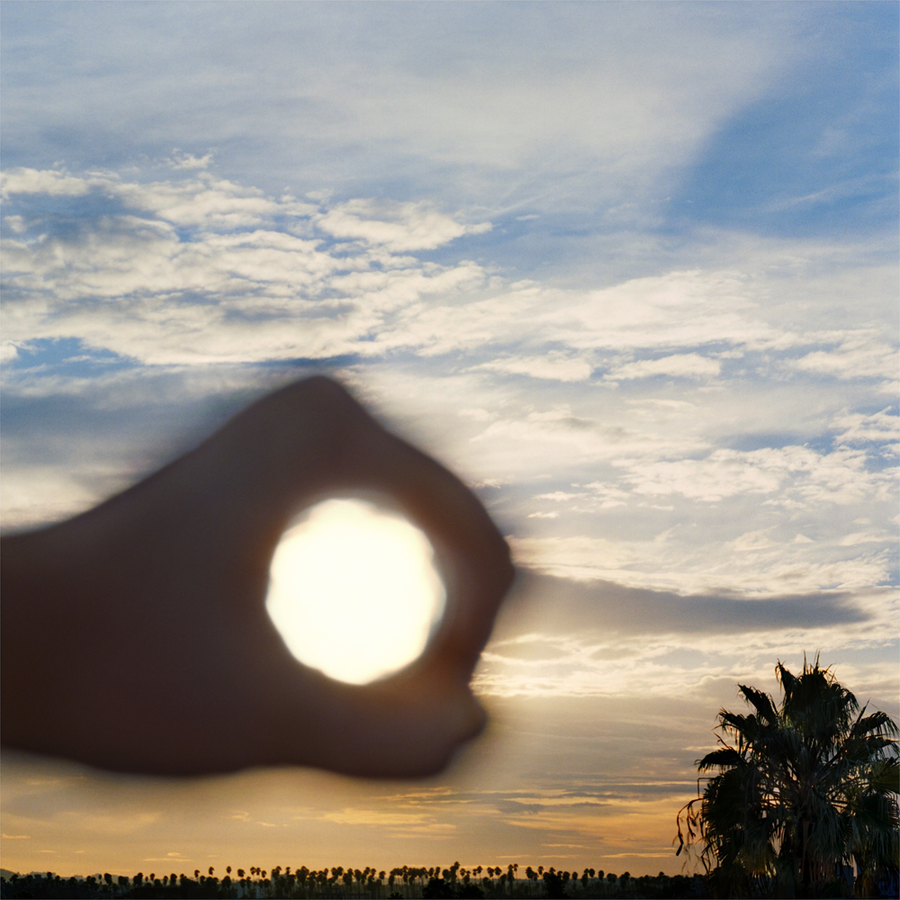 I Control the Sun #3, 2014, by Lilly McElroy. Archival pigment print of the artist's hand extended, encircling the rising sun, above palm trees.