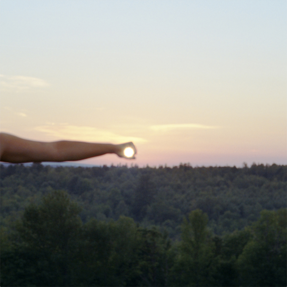 I Control the Sun #5, 2013, by Lilly McElroy. Archival pigment print of an extended hand holding the sun, above trees, in a pink, yellow and blue sky.