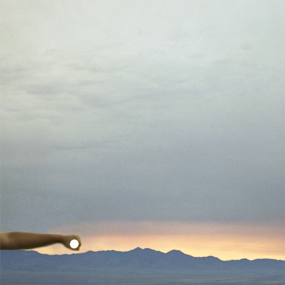 I Control the Sun #7, 2013, by Lilly McElroy. Archival pigment print of an extended arm holding the sun, above mountains, in a pink and yellow sunrise.