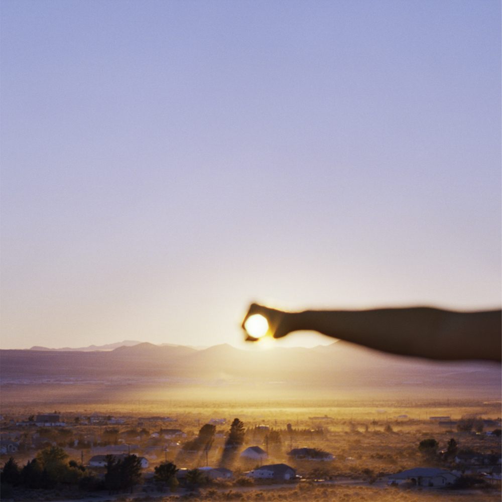 I Control the Sun #11, 2015, by Lilly McElroy. Archival pigment print of an extended hand holding the sun, above a golden hued landscape, at dusk.