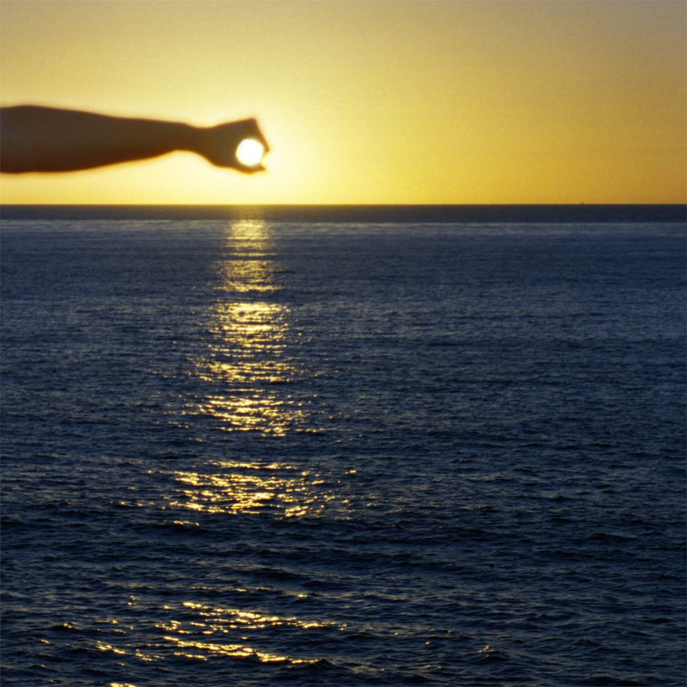 I Control the Sun #12, 2015, by Lilly McElroy. Archival pigment print of an extended hand holding the sun, in a golden sunset, casting onto the sea.