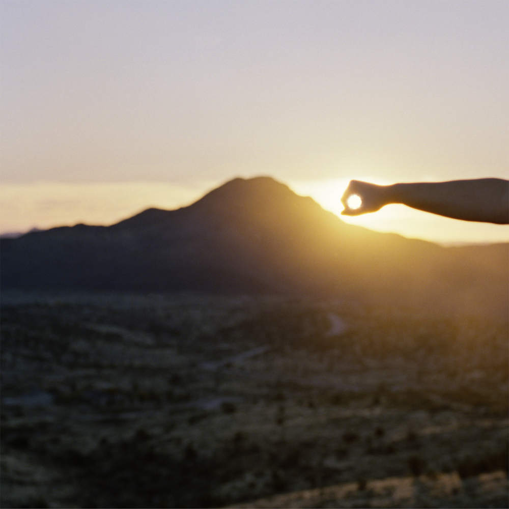 I Control the Sun #13, 2015, by Lilly McElroy. Archival pigment print of a hand holding the sun above a mountain, casting glowing ,yellow beams below.