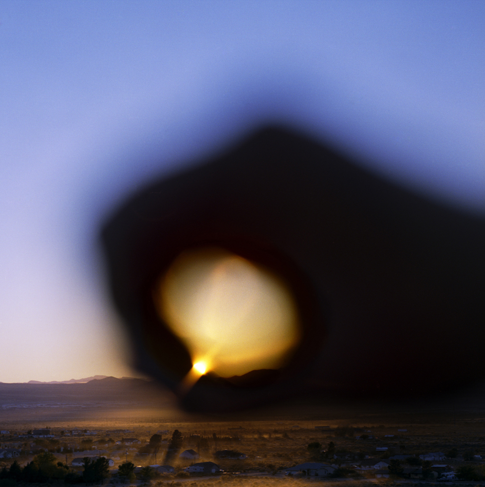 I Control the Sun #14, 2015, by Lilly McElroy. Archival pigment print of a hand holding a glowing sun, framed in a blue and purple sunset, above land.