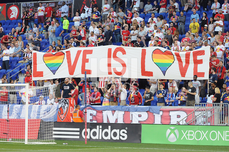 Fans hold up a sign in celebration of Pride Month