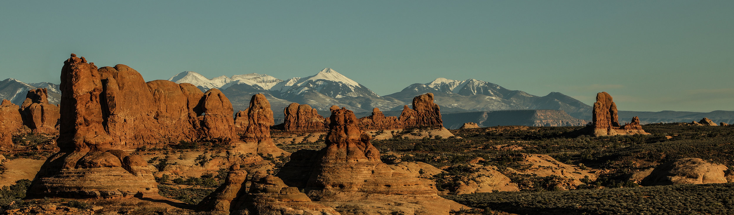 """""""A Tale of Two Seasons"""" was captured in Arches National Park just outside Moab, Utah and demonstrates what a change in elevation does to the climate. The desert in front of this image was around 4000 feet above sea level; whereas, the range in back was about 6500 feet above sea level."""