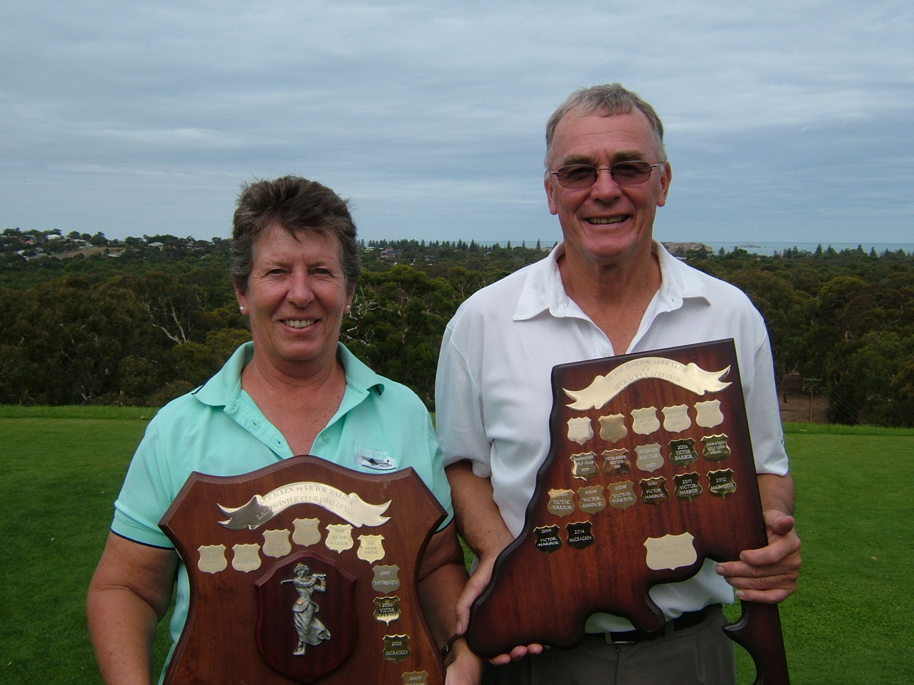 Victor Harbor Ladies Captain (Libby Bancroft) and Victor Harbor Club Captain (Bruce WATKINS) standing on our Iconic Holes Hall of Fame 1st Tee holding the trophies won.