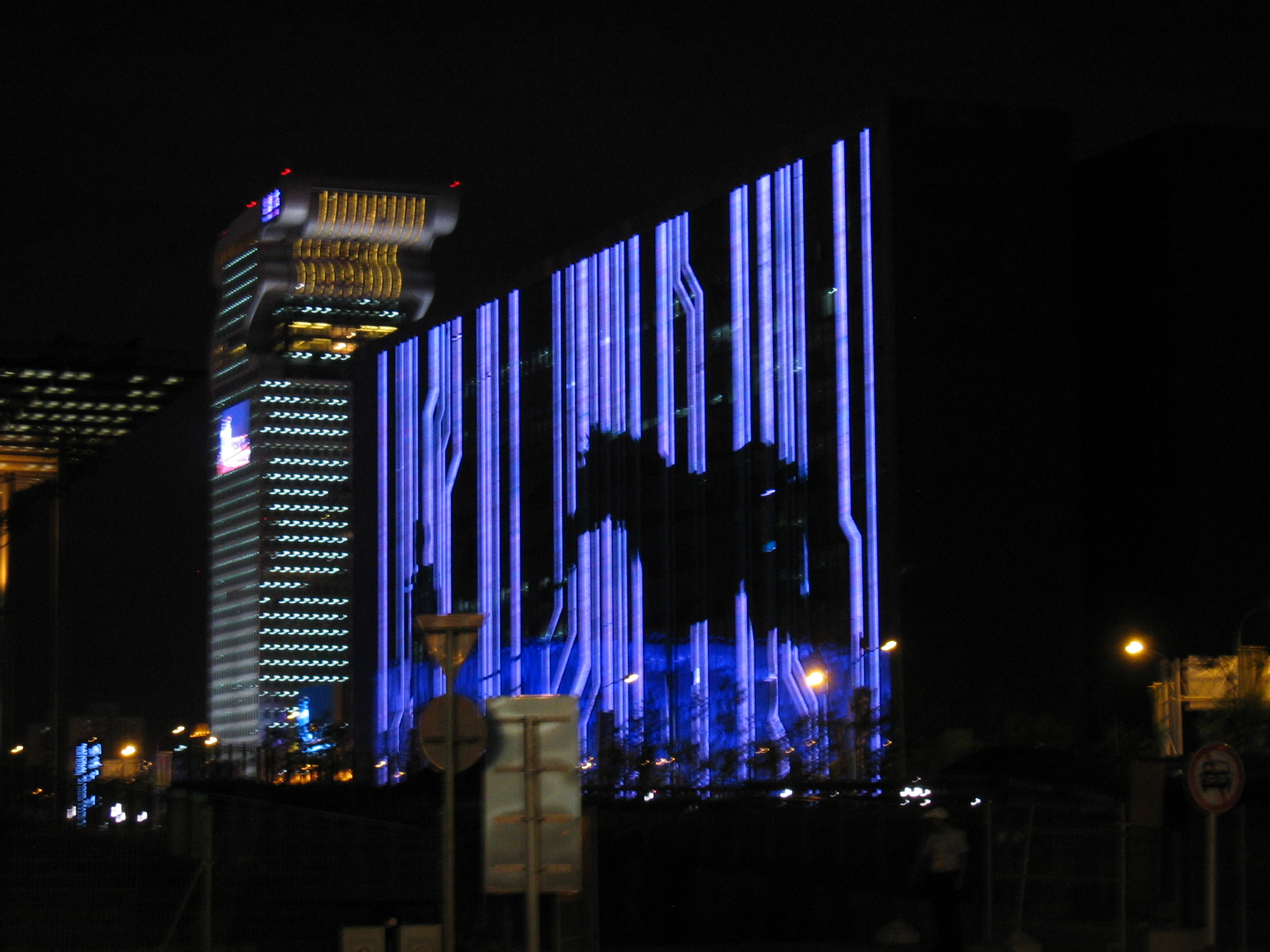 Creepy evil building by day, digital display by night