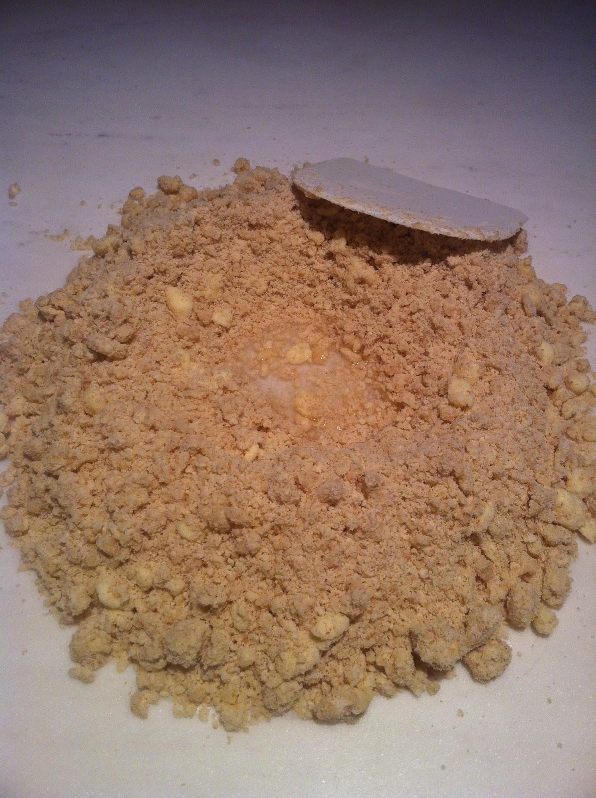Com um  cornet , pique os pedaços de manteiga rapidamente, misturando-os com os ingredientes, até formar uma farofa. Transfira esta farofa para uma superfície de trabalho limpa e faça um buraco no meio dela. Vá adicionando a água gelada aos poucos, à medida em que mistura tudo com o  cornet .